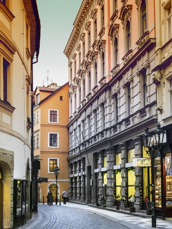 Narrow street with shops in Prague, a street with cobblestones in January in an evening atmosphere