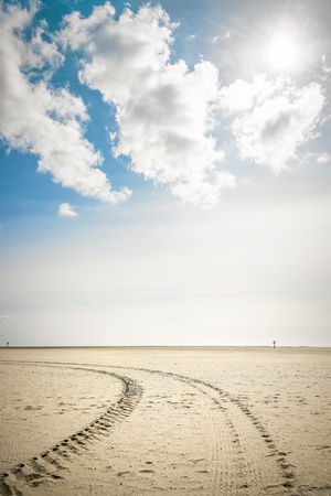 Tire tracks in the sand on the beach of St  Peter-Ording on a sunny day with blue sky and clouds photo