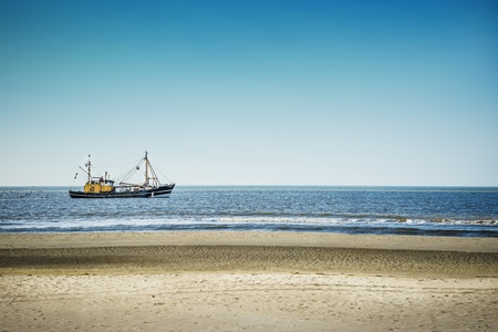 Trawlers in the North Sea on the beach of St  Peter-Ording on a sunny day photo