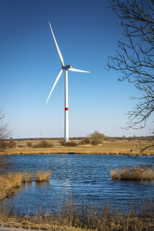 Windmill in a landscape with grass, trees and lake on a sunny day  Stock Photo - 19057421