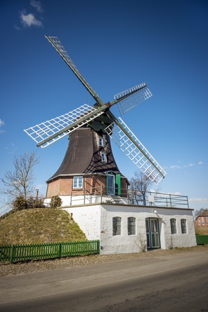 Windmill on a road in northern Germany in sunny weather and blue skies  Stock Photo - 19057414
