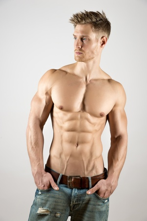 Blond young man with well trained body, abs and pecs and wearing a denim trousers look to the left