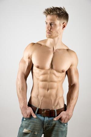 musculoso: Joven rubia con bien entrenado cuerpo, abdominales y pectorales y vistiendo un pantal�n de mezclilla mirada a la izquierda
