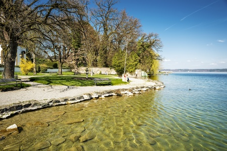 Shore of Lake Starnberg in Germany with gravel, trees, benches and people in sunny weather Stock fotó