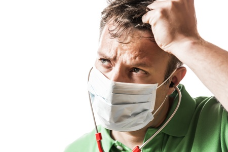 perspiring: Helpless, anxious and perspiring doctor in a green shirt with a red stethoscope and surgical mask Stock Photo
