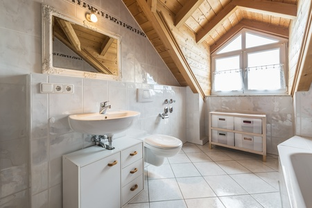 attic window: bathroom of a flat in attic with basin, mirror, light, window, toilet, bathtub, cabinets and wooden ceiling