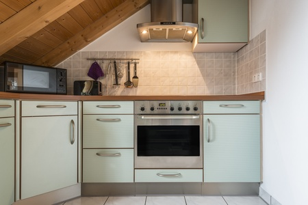 kitchen of a flat with oven, microwave, stove, hood, cabinets and wooden ceiling