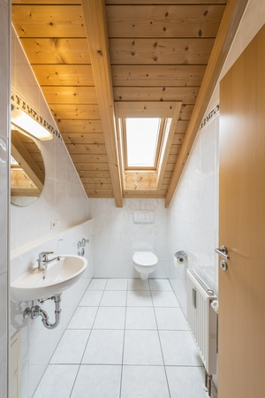 Picture of a white tiled restroom with basin, toilet, mirror, light and window photo