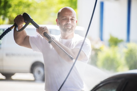 Bald man with a beard is washed with a pressure washer on a sunny day
