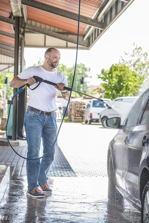 Bald man with a beard is washed with a pressure washer be black car on a sunny day Stock Photo