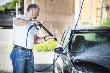 Bald man with a beard is washed with a pressure washer be black car photo