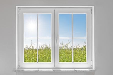 foto van een witte muur met witte gesloten raam binnen en buiten de groene weide met zon en blauwe hemel Stockfoto