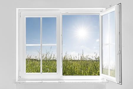 foto van een witte muur met witte half open raam binnen en buiten de groene weide met zon en blauwe hemel Stockfoto