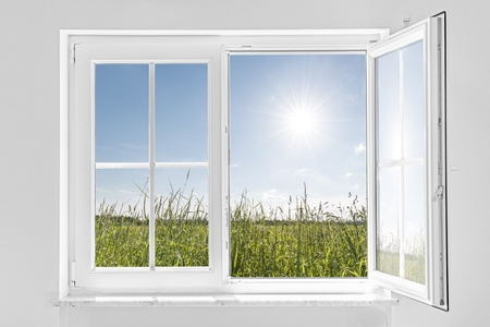interior window: picture of a white wall with white half open window indoor and outside green meadow with sun and blue sky