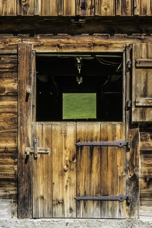 Picture of a wooden door of a stable in the Alps
