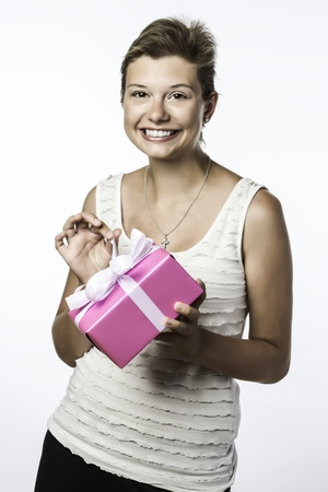 Pretty young brunette girl with brown eyes opens a birthday or christmas present photo