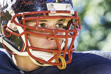 american football: Portrait of a American Football Player with a heavily worn helmet