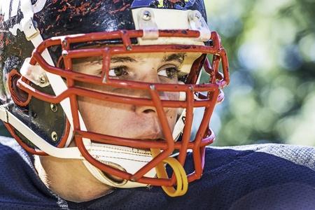 football play: Ritratto di un Giocatore di football americano con un casco fortemente usurati