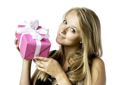 Pretty blond young girl with blue eyes has a birthday or christmas present photo