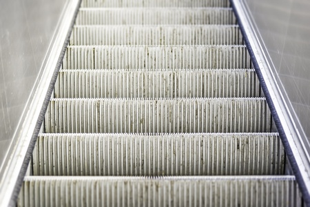 Closeup of a heavily used and worn escalator stairs photo