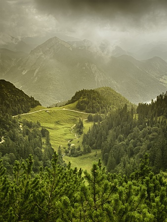 View from the mountain named Herzogstand to green meadow with trees and dark clouds in Bavaria, Germany photo