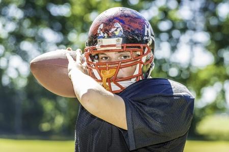 サッカーと激しく消耗したヘルメットのアメリカのフットボール選手