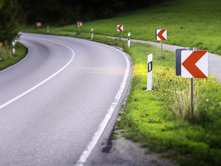 Dangerous road curve with warning signs photo
