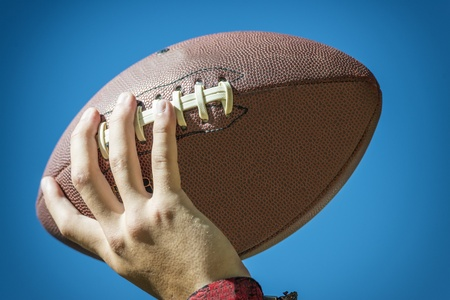 closeup of a hand with american football and blue sky in background