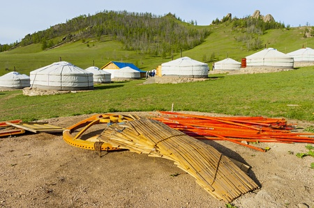 nomad: Components of a yurt in the foreground and in the background ready yurts Stock Photo