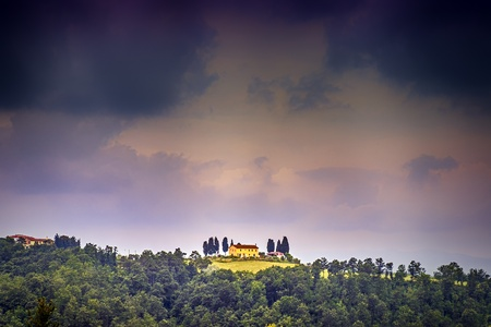 picture of a landscape with house and dark storm clouds in tuscany, italy photo