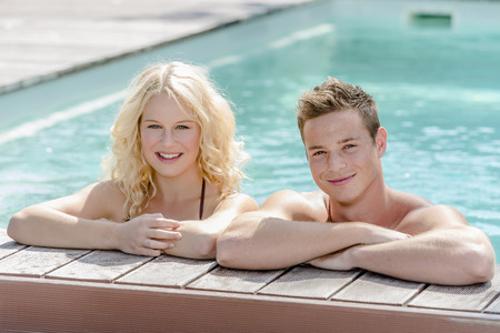 bikini couple: Young blond girl and handsome boy on the edge of a swimming pool