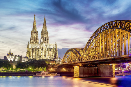 Illuminated Dom in Cologne with bridge and rhine at sunset