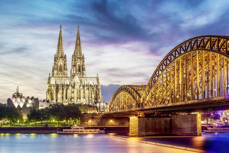 Verlichte Dom in Keulen met brug en de rijn bij zonsondergang Stockfoto
