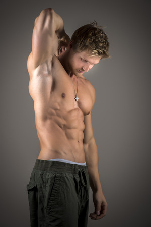 Blond young athlete with strong muscles is posing