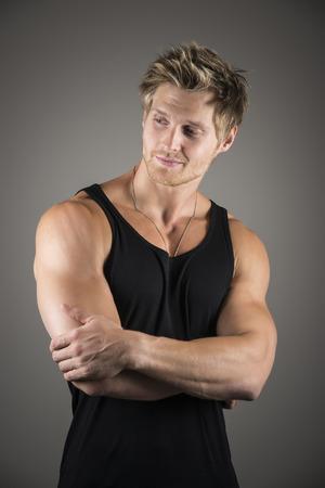 Portret van een knappe jonge man met sterke spieren en zwarte shirt