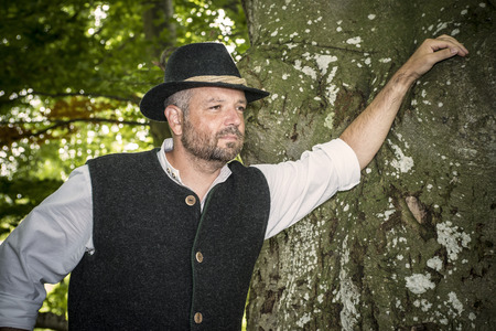 Man with traditional Bavarian costume is standing in a forest photo