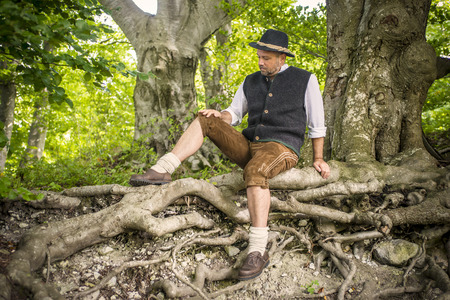 Bavarian man with traditional costume is sitting in a forest photo