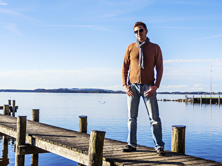 Man with sunglasses on a landing stage at a lake in sunny weather photo
