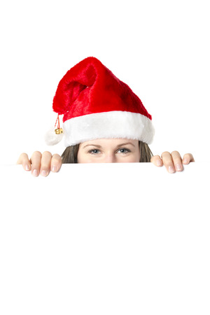 Woman with Santa Claus costume is hidden behind a empty white board, isolated on white photo