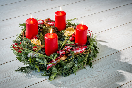 Advent wreath of twigs with four burning red candles and various ornaments photo