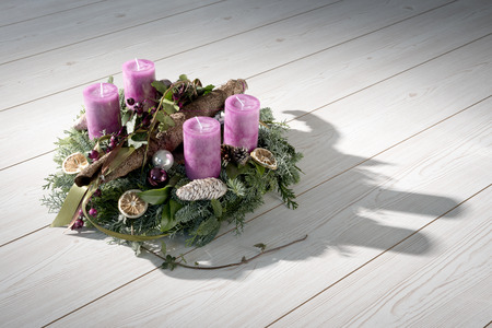 Advent wreath of twigs with purple candles and various ornaments