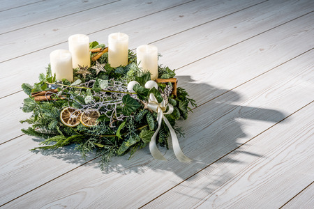 Advent wreath of twigs with white candles and various ornaments photo