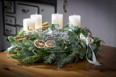 Komst krans van takjes met witte kaarsen en diverse ornamenten Stockfoto