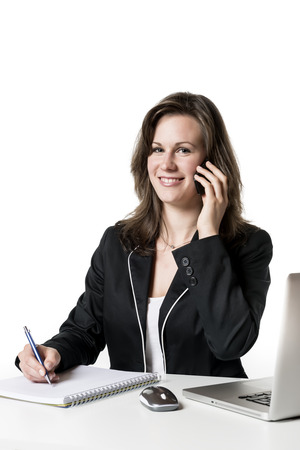 Businesswoman sitting at desk in office and on the phone photo