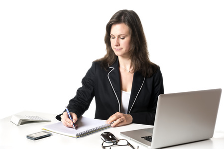 Businesswoman sitting at desk in office, writing something on a pad, isolated on white background photo