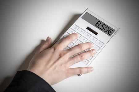 minimum wage: Mujeres mano con la calculadora, lo que indica que el salario m�nimo alem�n prevista de 8,50 ? Foto de archivo