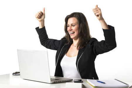 Happy woman sitting in office at desk in front of her laptop and holding her thumbs up photo