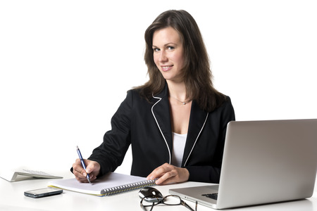 Smiling Businesswoman sitting at desk in office, writing something on a pad, isolated on white background photo