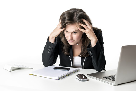 Stressed business woman sitting in office at desk, looking at laptop and holding his hands to his head photo