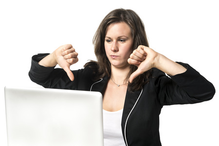 Woman sitting dissatisfied in office at desk, holding their thumbs down photo